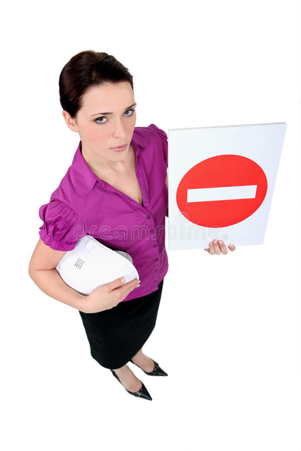 Architect holding a stop sign. A female architect holding a stop sign stock image