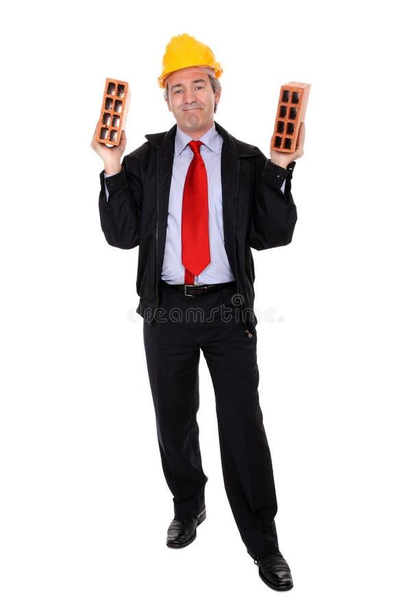 Architect holding two bricks royalty free stock photos