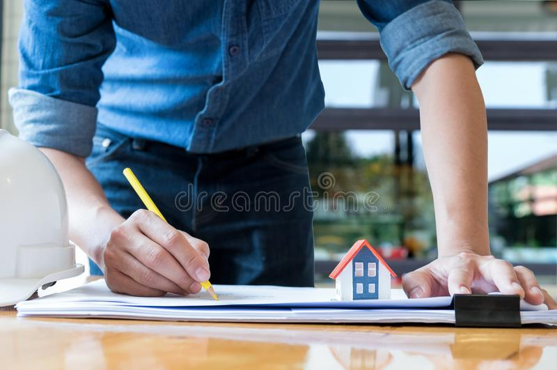 Architect holding a yellow pencil drawing house plan with model royalty free stock photo