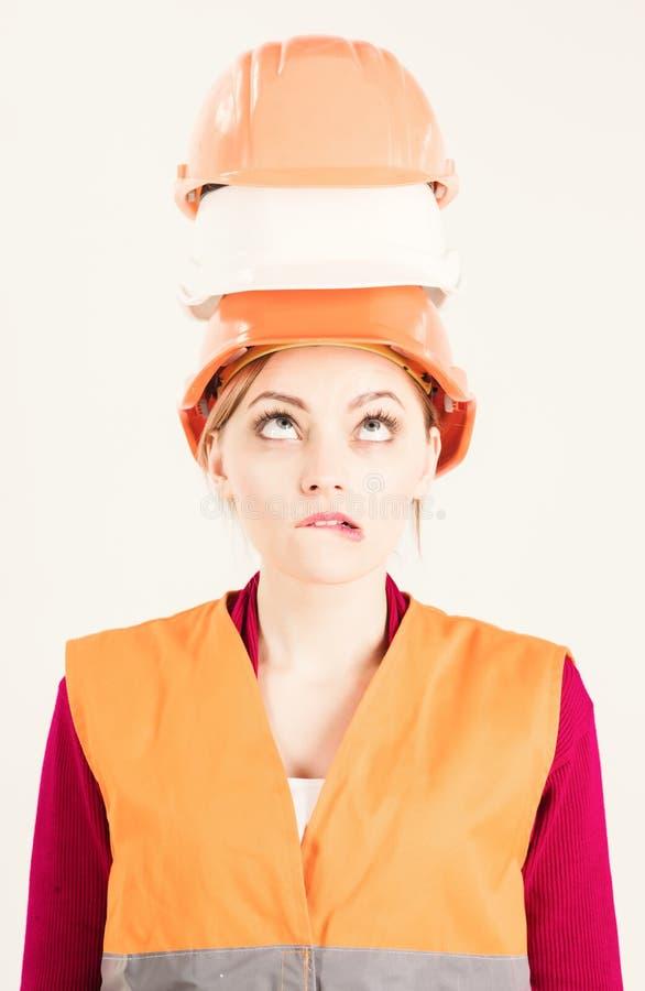 Architect, ingenieur, bouwer over onroerende goederen die bouw wordt geschokt, Vrouw met verward grimasgezicht in eenvormig, wit stock afbeeldingen