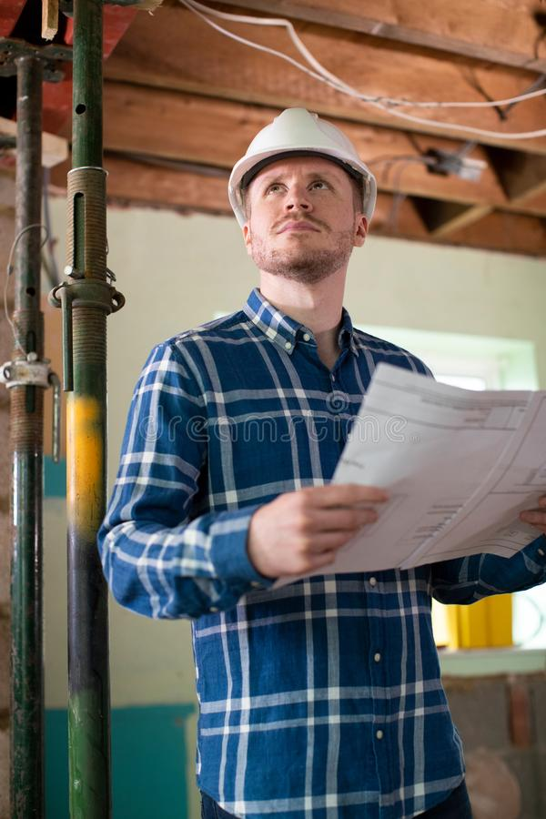 Architect Inside House Being Renovated Studying Plans stock photo