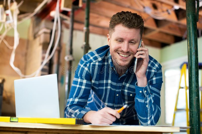Architect Inside House Being Renovated Working On Plans Using Laptop And Talking On Cellphone royalty free stock images