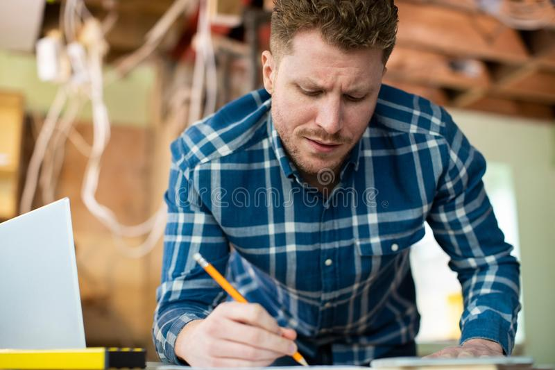 Architect Inside House Being Renovated Working On Plans Using Laptop stock photo