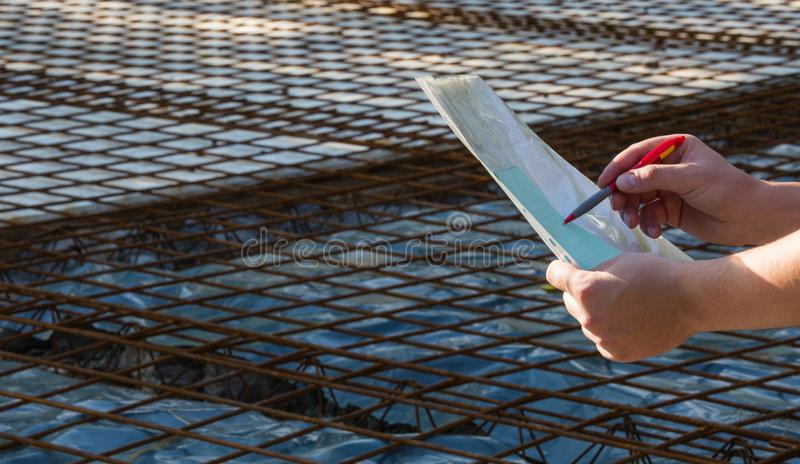 The architect keeps the papers with the project and looks at the stock photos