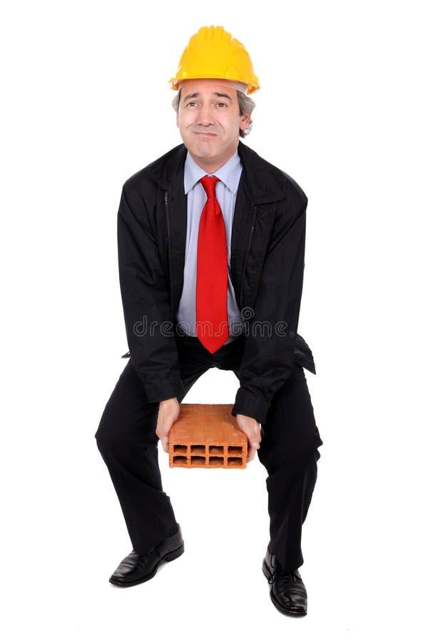 Architect lifting a brick royalty free stock image