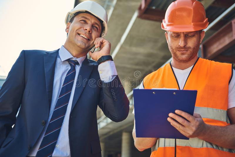 Architect is locating on construction site with worker man. Smiling project manager is talking on smartphone while foreman writing on paper royalty free stock photography