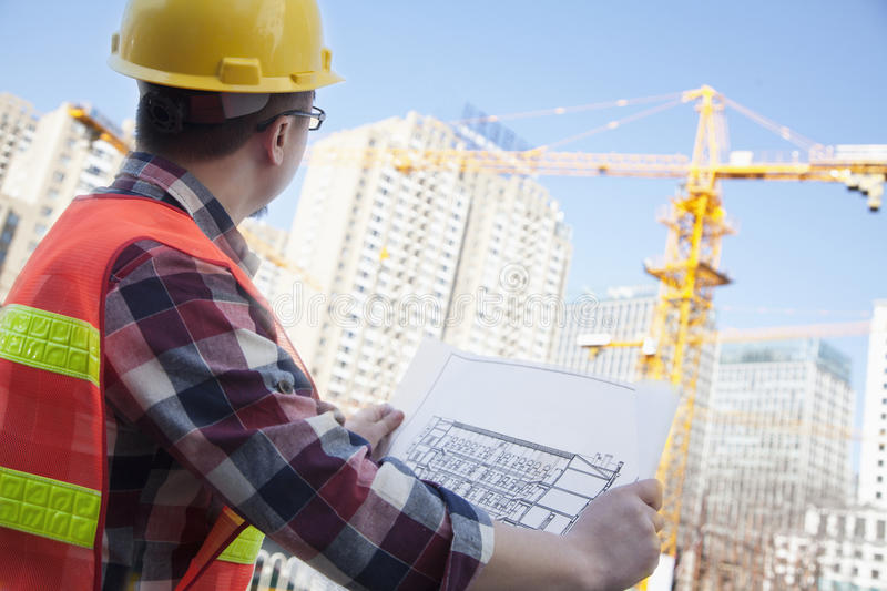 Architect looking at a blueprint outdoors at a construction site royalty free stock photo