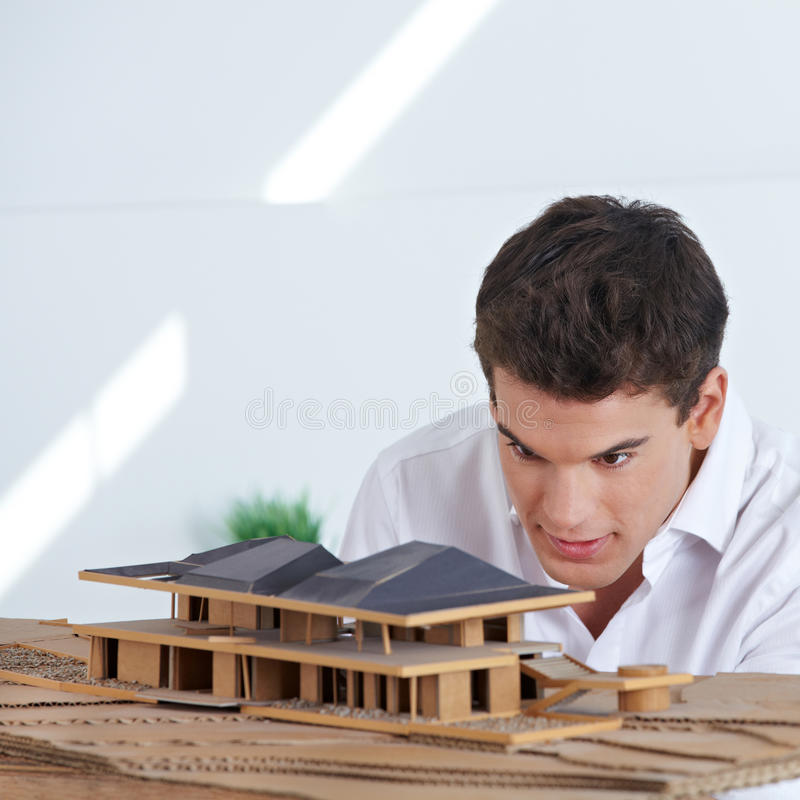 Architect looking at house model royalty free stock photography