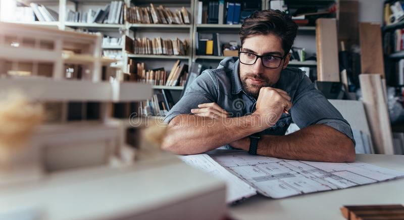 Architect looking at house model on desk royalty free stock photo