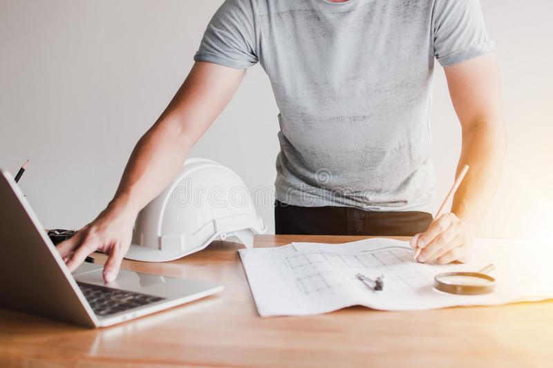 Architect looking on laptop an design and drawing on blue print royalty free stock photos