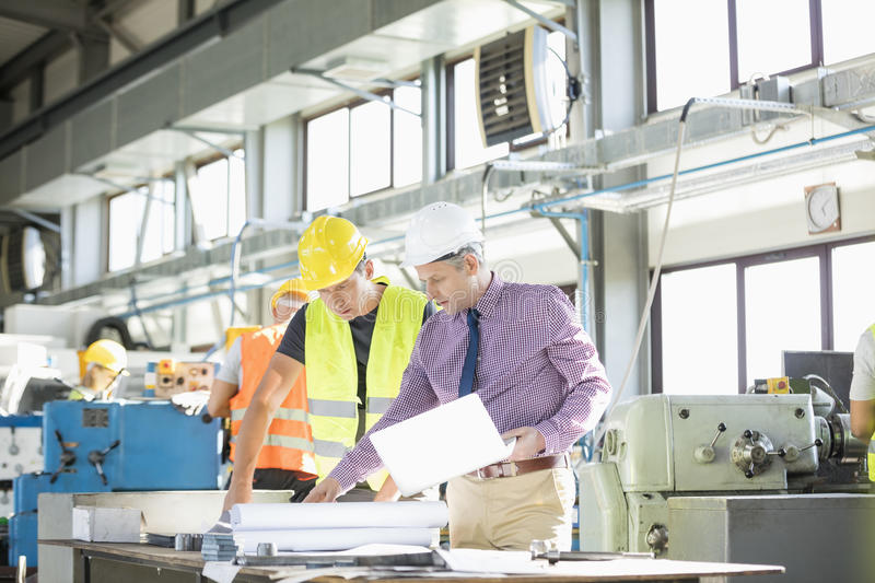 Architect and manual worker examining blueprint at table in industry stock photos