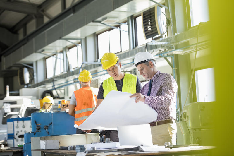 Architect and manual worker reading blueprint at table in industry stock photos