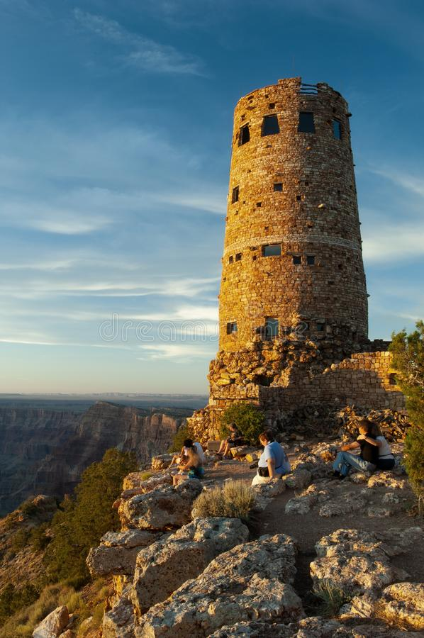 Visitors look out at the Grand Canyon beside the stone Watchtower in Grand Canyon National Park. Named a UNESCO World Heritage Site in 1979, the Grand Canyon royalty free stock photo