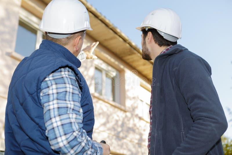 Architect and mason inspecting exterior house. Architect and mason inspecting the exterior of the house royalty free stock image