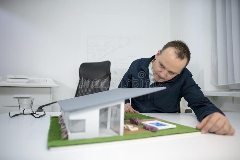 Architect looking at a model house in office stock images