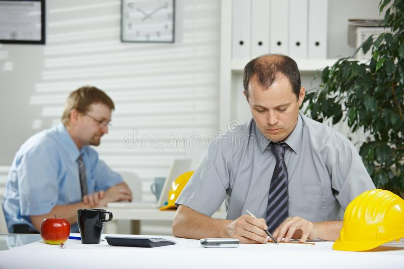 Architect planning at desk stock image