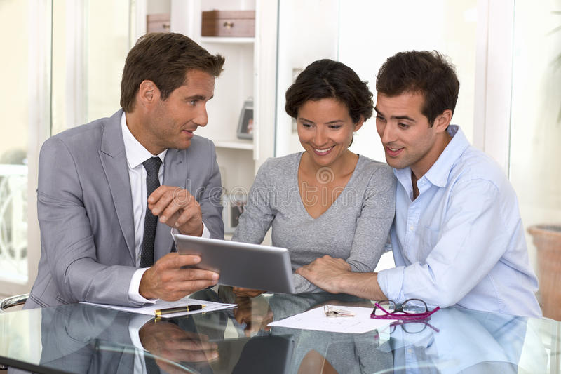 Architect presenting a new project to a smiling young couple royalty free stock photo