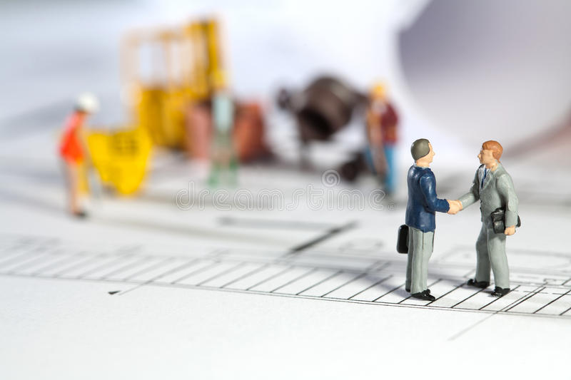 Architect and property owner shaking hands. Miniature models of an architect and property owner shaking hands outside the building site of his new house royalty free stock image