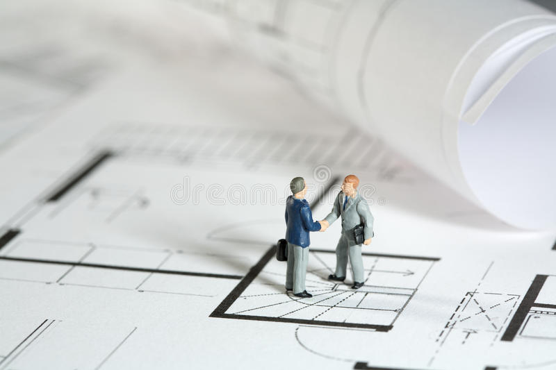 Architect and property owner shaking hands. Miniature models of an architect and property owner shaking hands outside the building site of his new house royalty free stock photos