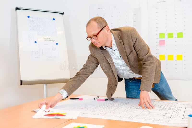 Architect Reaching For Document terwijl het Werken aan Blauwdruk royalty-vrije stock afbeelding