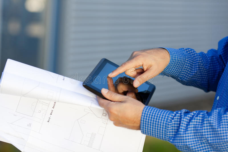 Architect's Hands Holding Blueprint While Using Digital Tablet royalty free stock image
