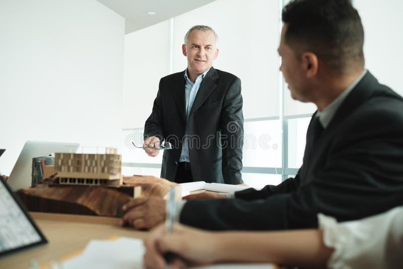 Architect Showing Miniature Building op Commerciële Vergadering met Cliënt royalty-vrije stock foto