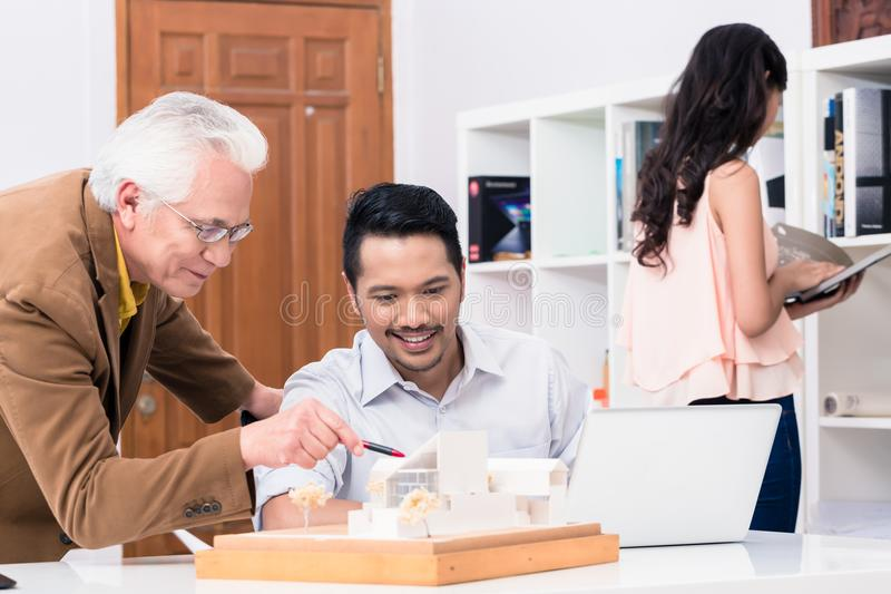 Architect showing to his colleague the project of a residential royalty free stock photo