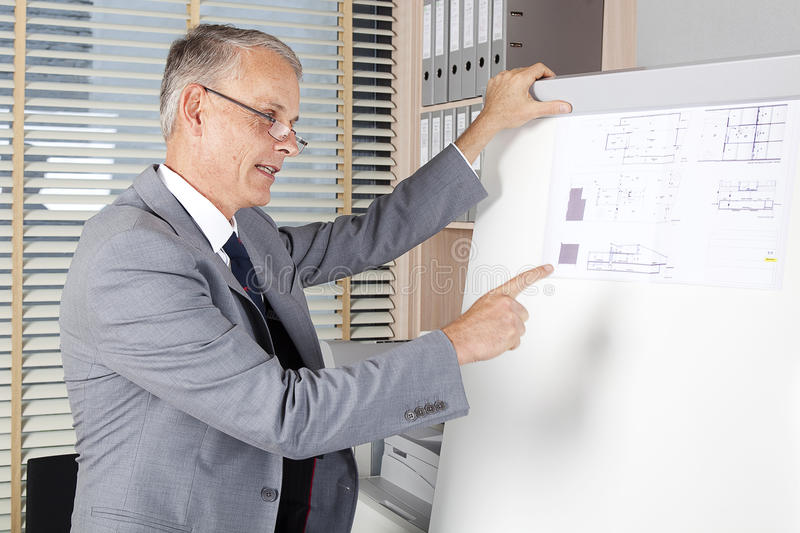 Architect shows plans. Office situation royalty free stock photography
