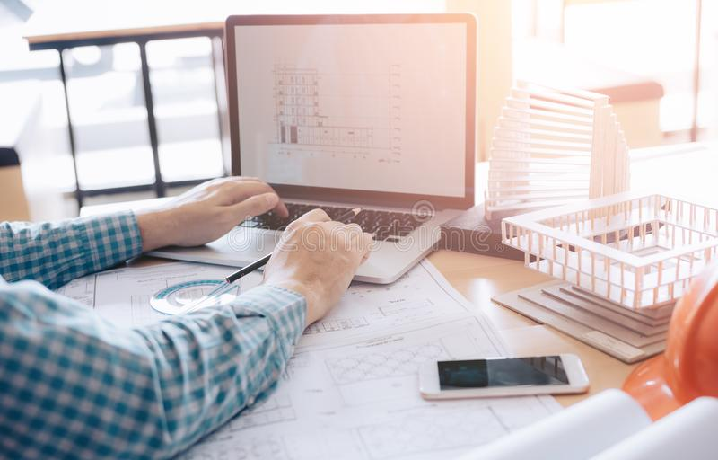 Architect sitting in modern office using computer working project and looking blueprint on screen. stock photos