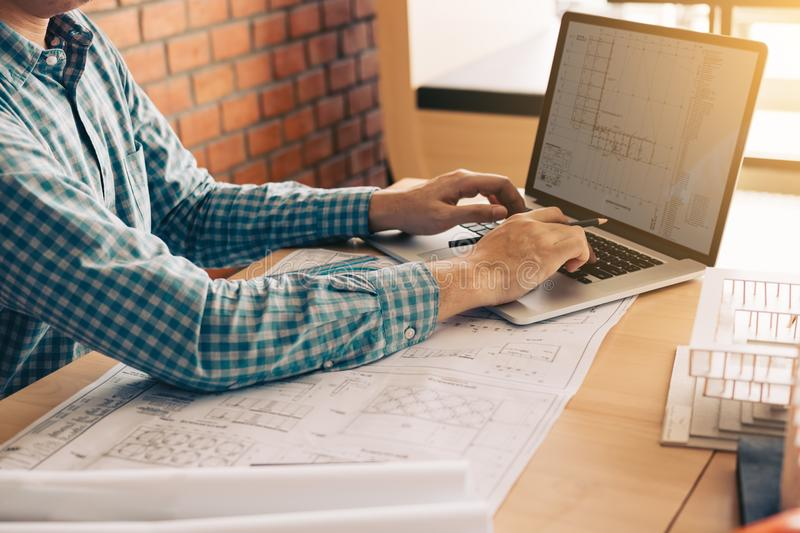 Architect sitting in modern office using computer working project and looking blueprint on screen. royalty free stock photo