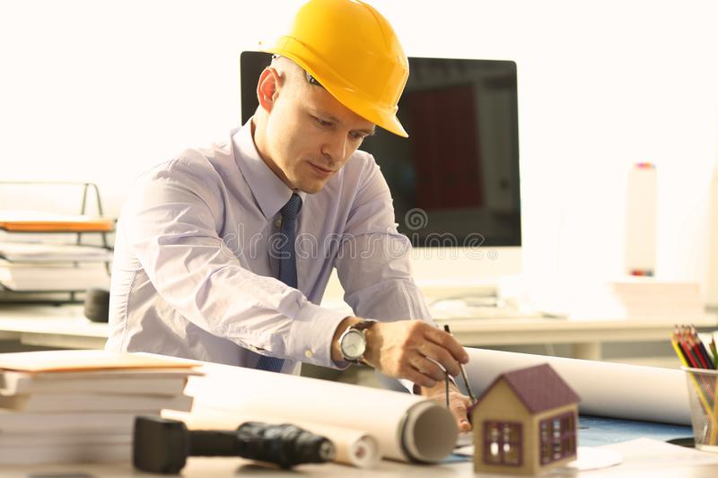 Architect Sketching Creative Object Reconstruction. Safe Building Design Concept. Contractor Engineer Using Measuring Tool Drawing Blueprint. Young Busy Man in stock image