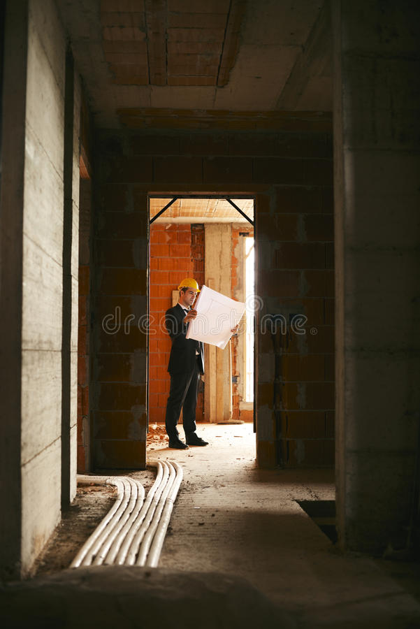 Download Architect Standing In House Under Construction With Building Pla Stock Photo - Image: 31809672