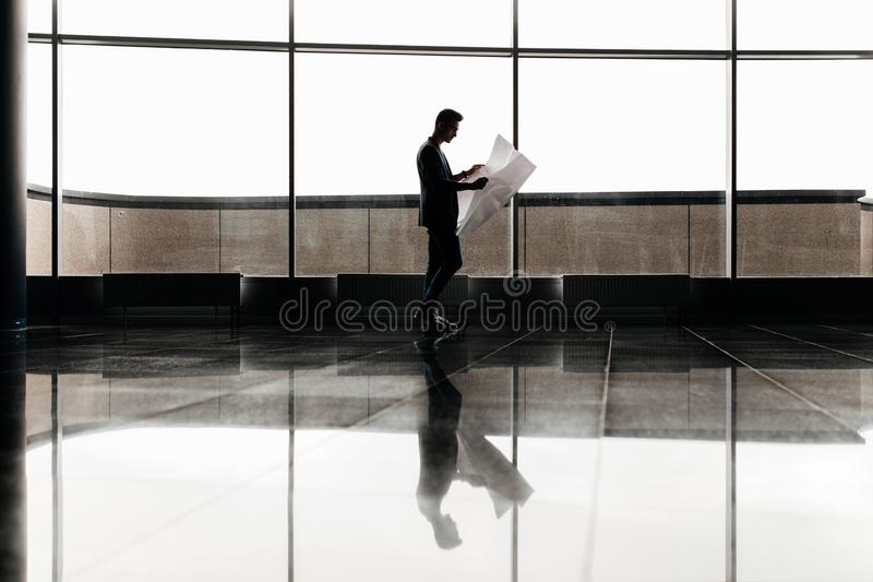 Architect in stylish clothes holds sheet with drawing in his hand and talks by phone on the background of a modern glass stock image
