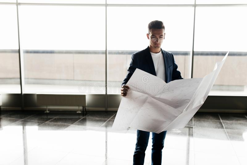 Architect in stylish clothes holds sheet with drawing in his hand and talks by phone on the background of a modern glass royalty free stock images