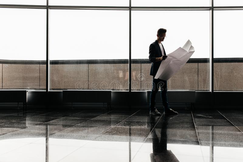 Architect in stylish clothes holds sheet with drawing in his hand and talks by phone on the background of a modern glass stock photography