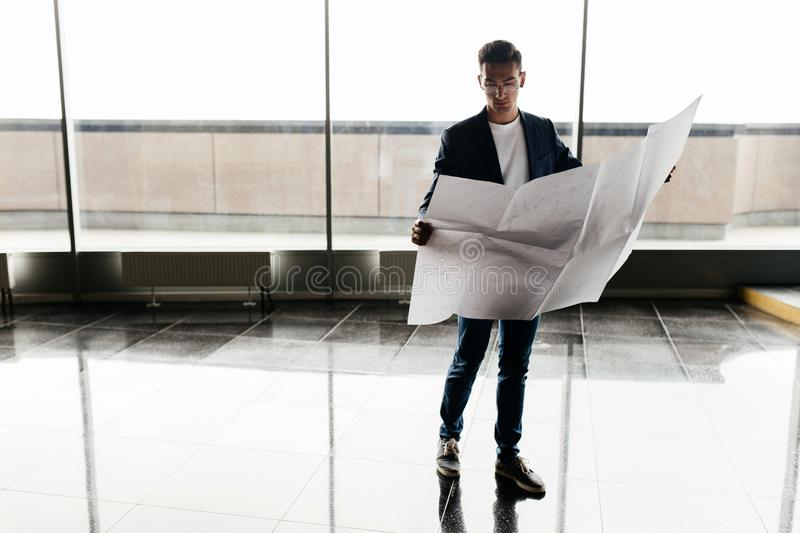Architect in stylish clothes holds sheet with drawing in his hand and talks by phone on the background of a modern glass stock photos