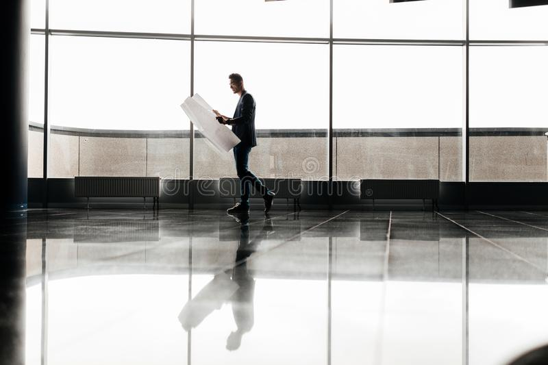 Architect in stylish clothes holds sheet with drawing in his hand and talks by phone on the background of a modern glass royalty free stock photo