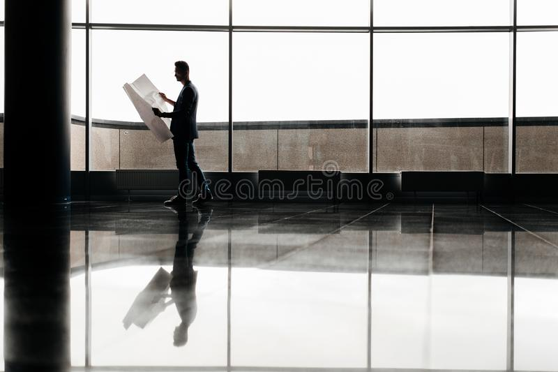 Architect in stylish clothes holds sheet with drawing in his hand and talks by phone on the background of a modern glass stock photo