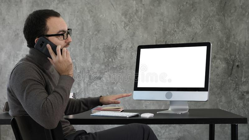 Architect talking on the phone discussing the project on the screen of the computer. White Display. royalty free stock photography