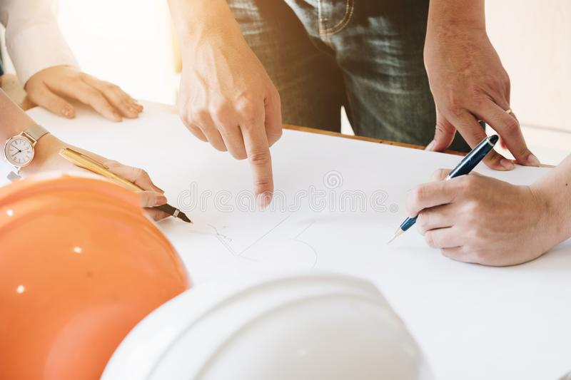 Architect Team Brainstorming Planning Design, Civil engineer sketching a blueprint of construction project with small house model stock photos
