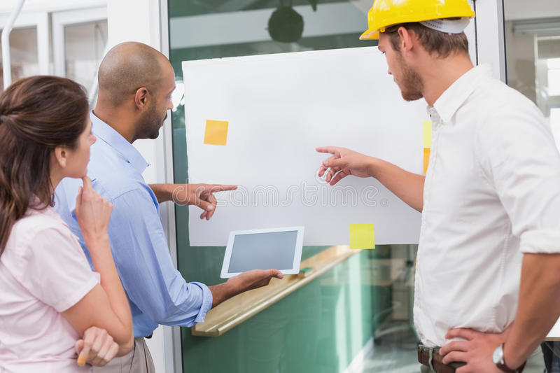 Architect team brainstorming together using digital tablet royalty free stock photo