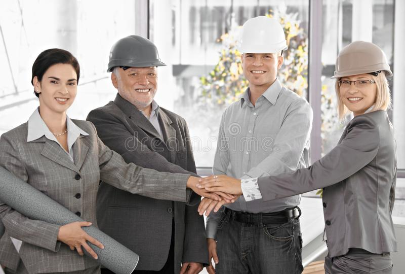 Architect team in office holding hands in unity royalty free stock images