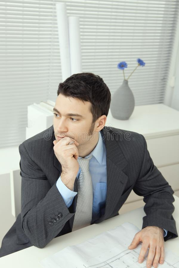 Architect thinking. Architect wearing grey suit sitting at office desk, thinking over floor plan. Overhead shot royalty free stock images
