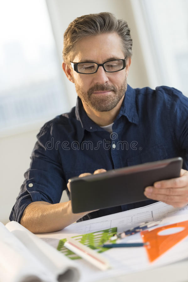 Architect Using Digital Tablet At Desk In Office royalty free stock image