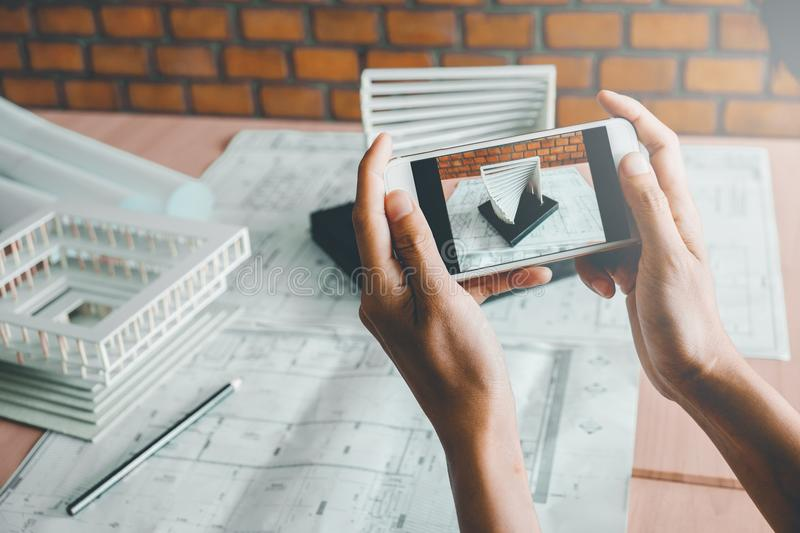 Architect using smart phone photograph model building in office. royalty free stock photo