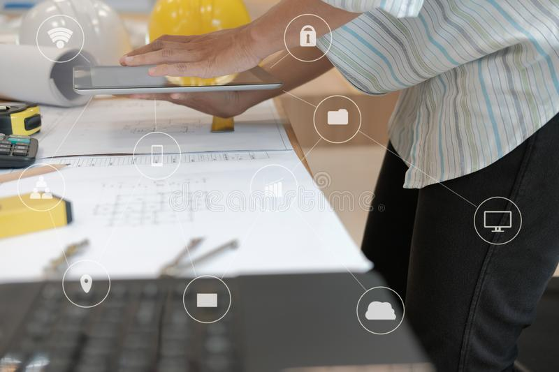 architect using tablet. engineer working on house blueprint of real estate project at workplace. building construction concept royalty free stock image