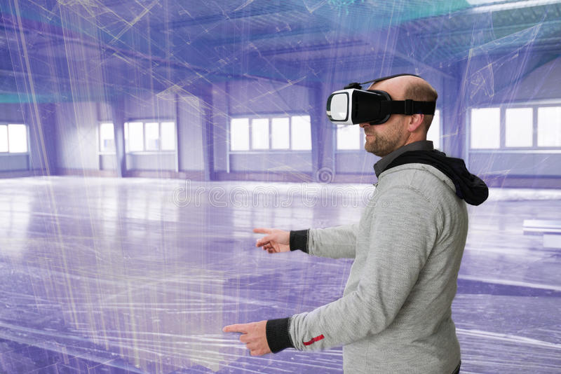 Architect with VR visor exploring industrial building environment. With blueprint lines overlaying the real scenario stock photography