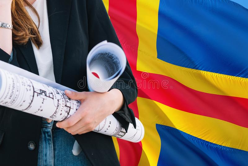 Architect woman holding blueprint against Aland Islands waving flag background. Construction and architecture concept.  stock photo