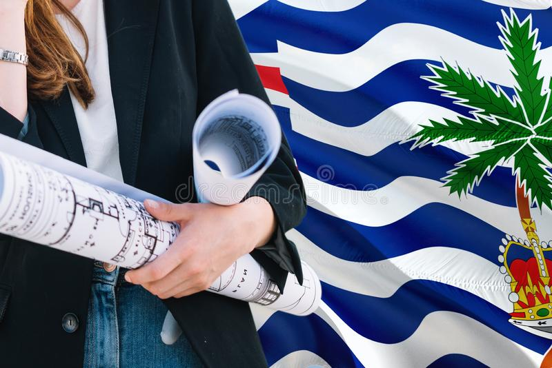 Architect woman holding blueprint against British Indian Ocean Territory waving flag background. Construction and architecture royalty free stock photo