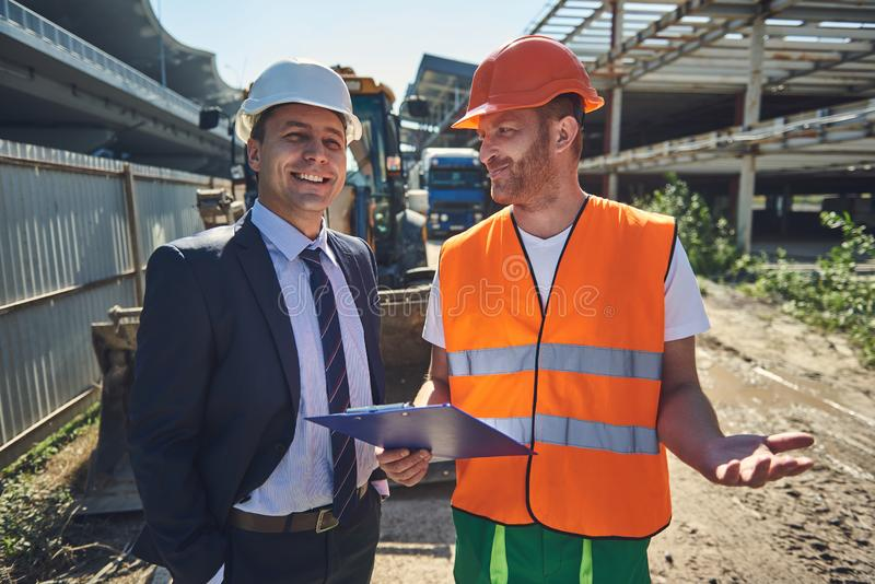Architect and worker are standing at construction site stock photos